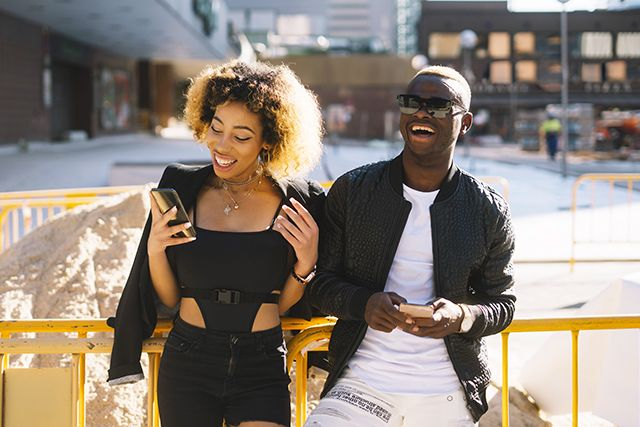 woman & man on phones laughing together