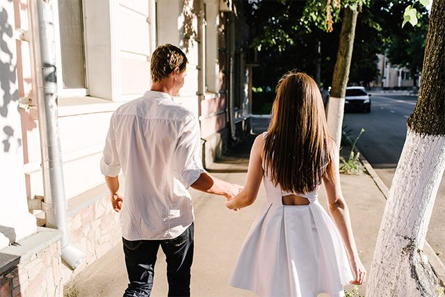 man & woman holding hands on sidewalk