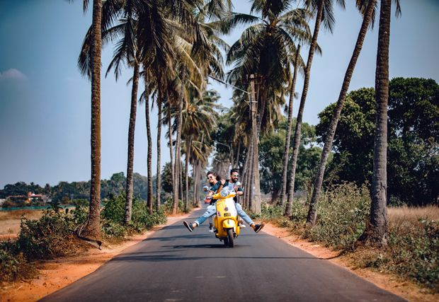 couple driving yellow scooter down road