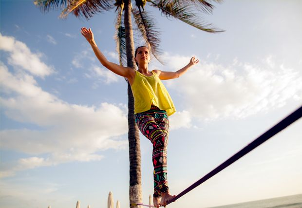 woman in yellow top balancing on tightrope
