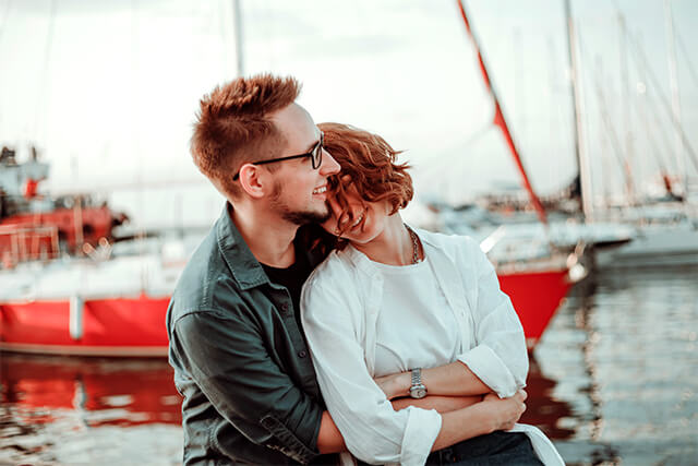 couple cuddling next to ocean